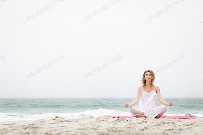 Front view of beautiful caucasian woman performing yoga with yoga mat at beach on sunny day