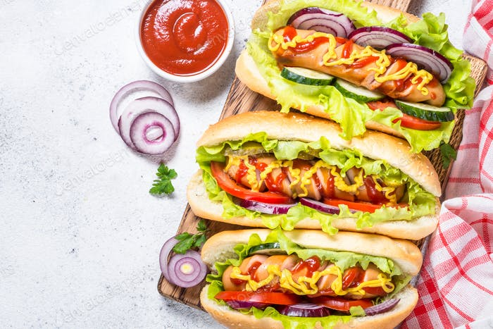 Hot dog with fresh vegetables on white top view