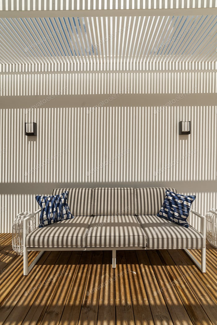 Detail of couch with shadow stipes in modern villa patio