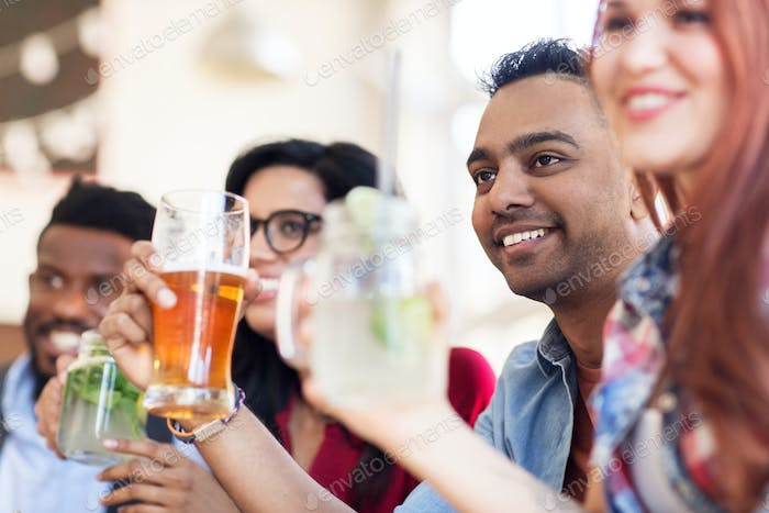 happy friends with drinks at restaurant