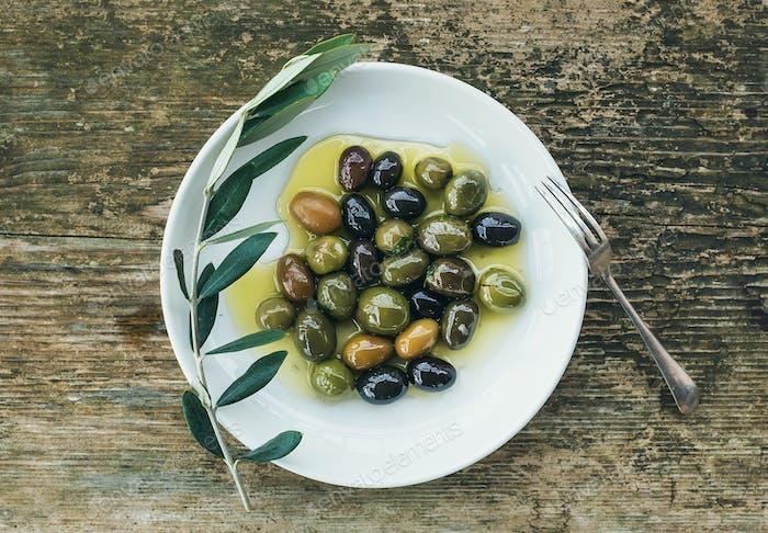 Ein Teller mit mediterranen Oliven in Olivenöl mit einem Zweig von ol
