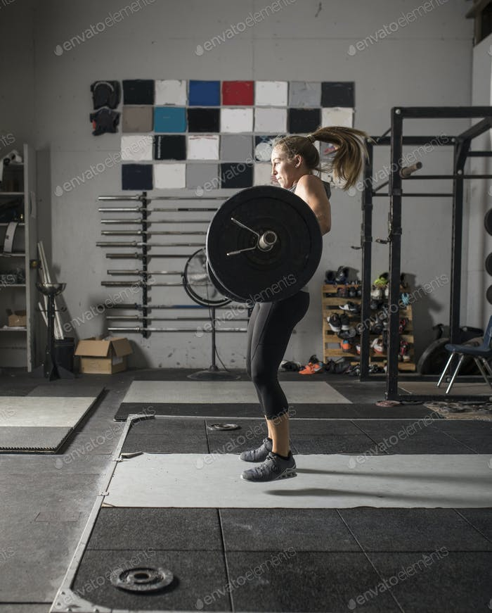 Action shot of female weight lifter doing snatch.