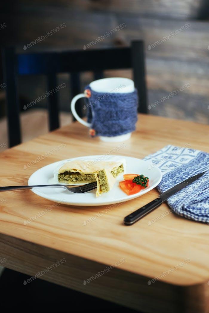 Kuchen mit Spinat und Tomatenscheibe auf Holztisch.