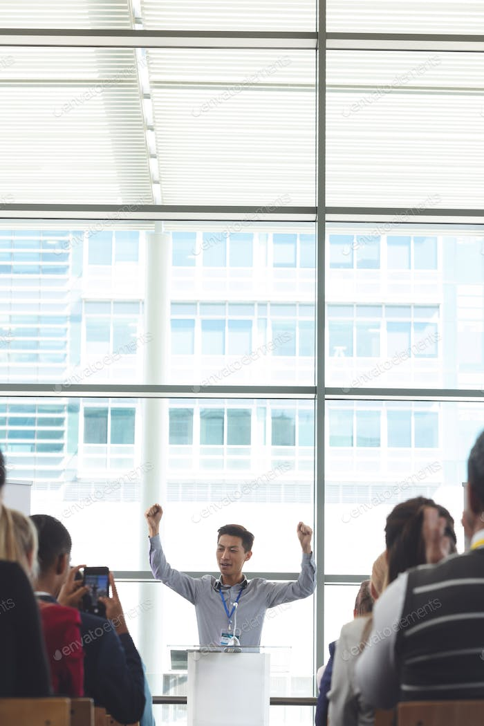 Businessman cheering while speaking in front of business professionals at seminar in office building