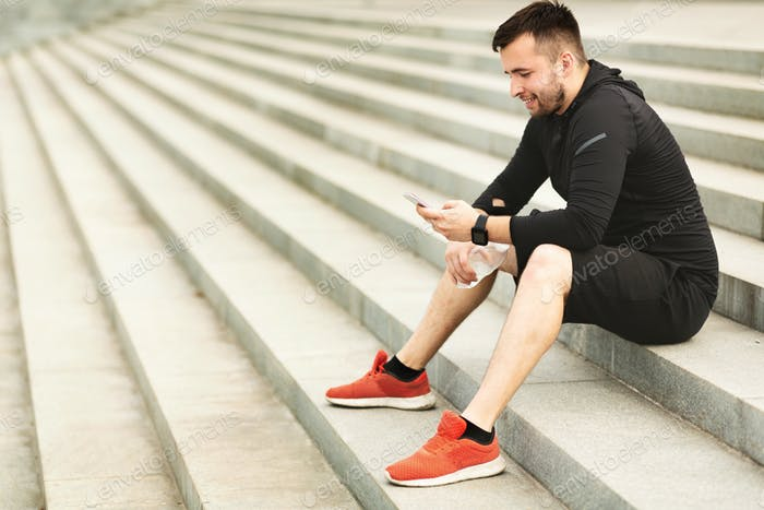 Man texting on cellphone while sitting on stairs after jogging