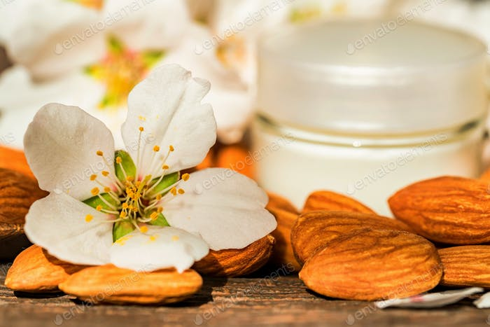 Almonds, face cream and white flowers