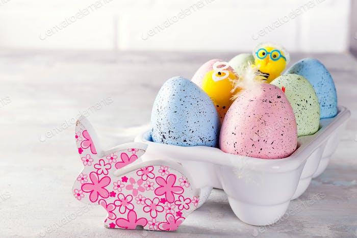 Organic colorful easter eggs with cutie bunny in porcelain decorative box on white. Holiday Easter