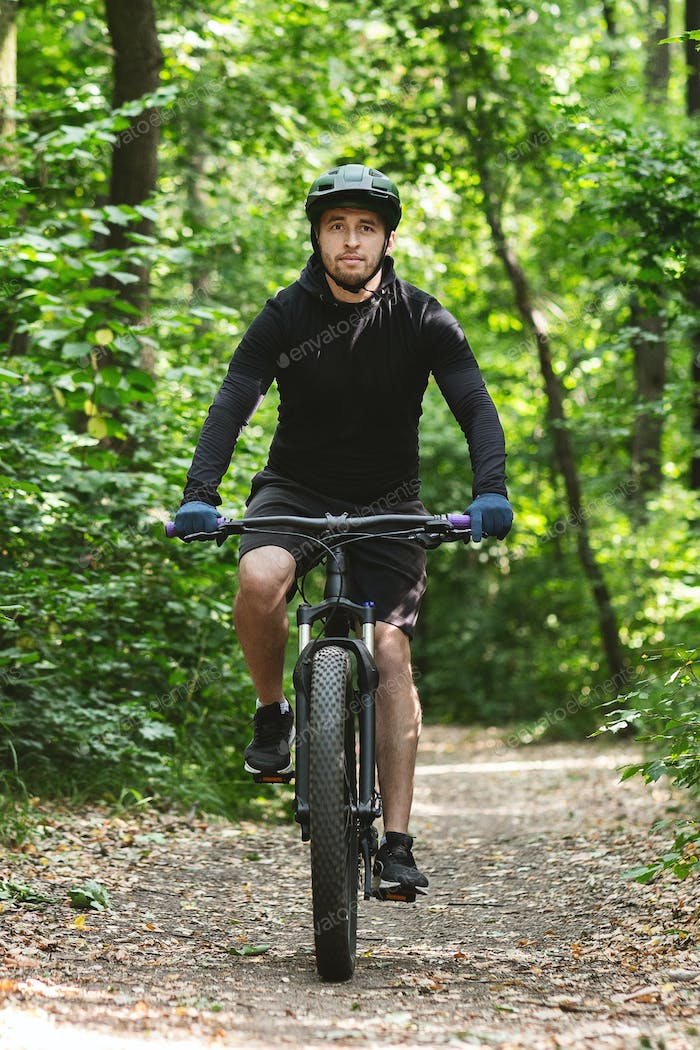 Handsome man riding bike down the forest trail