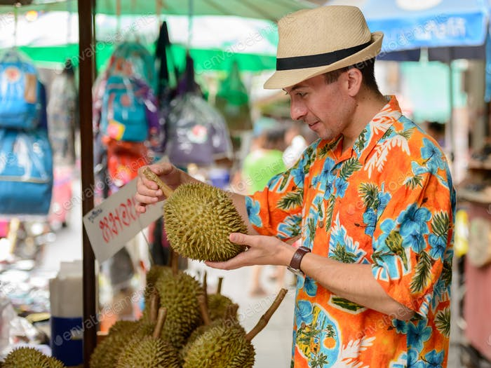 Happy young handsome tourist man buying durian at the street market