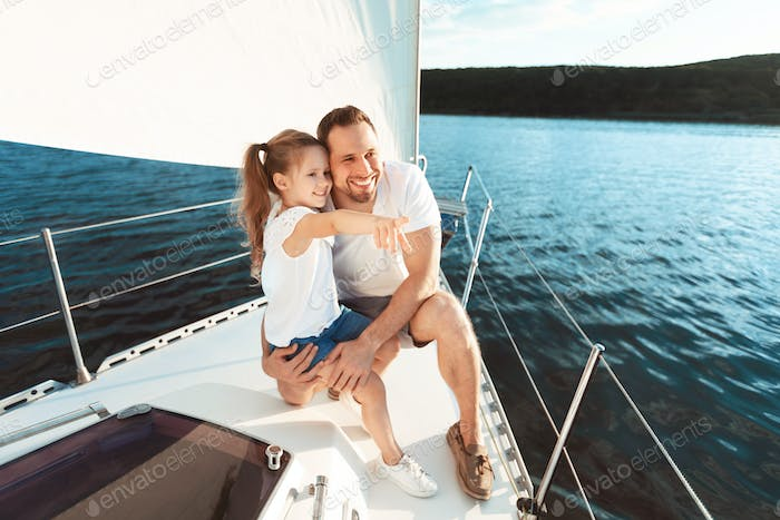 Cheerful Father And Daughter Sitting On Deck Enjoying Yacht Tour