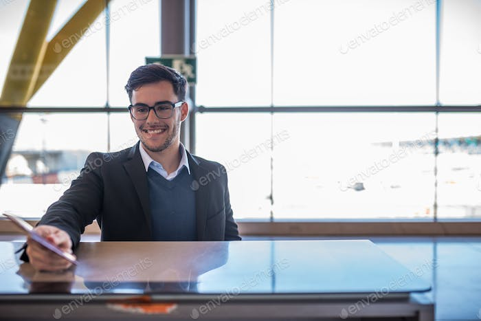 attractive young man check-in at the airport with his passport