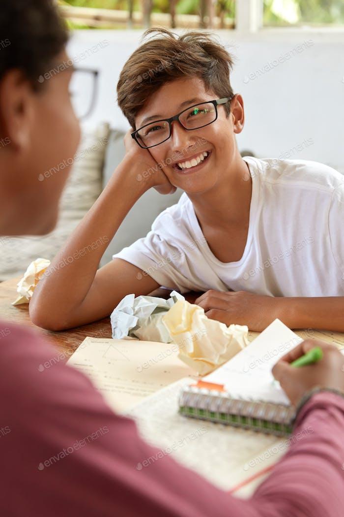 Die Rückansicht einer nicht wiederzuerkennenden Frau erklärt asiatischen Jugendlichen während der Zusammenarbeit einige Informationen.