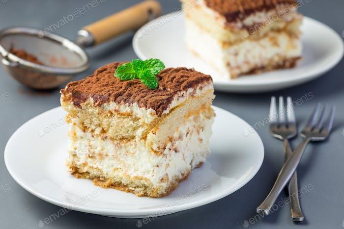 Two piece of traditional italian Tiramisu dessert cake on a whit