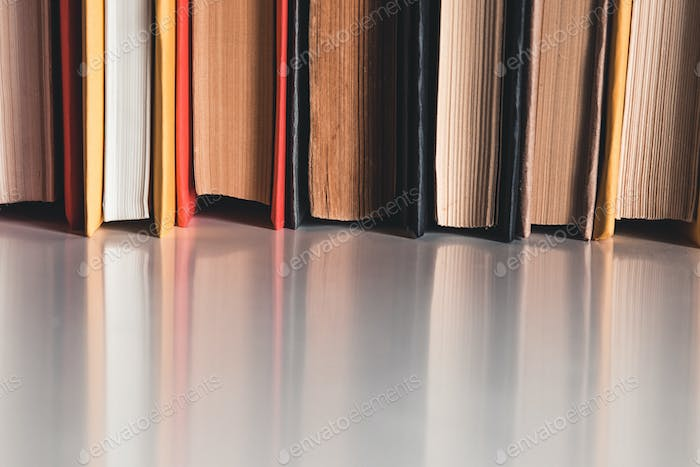 Stack of hardback books on the white table on gray wall background. Search for relevant