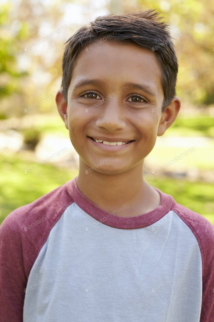Smiling mixed race boy in park looking to camera, vertical