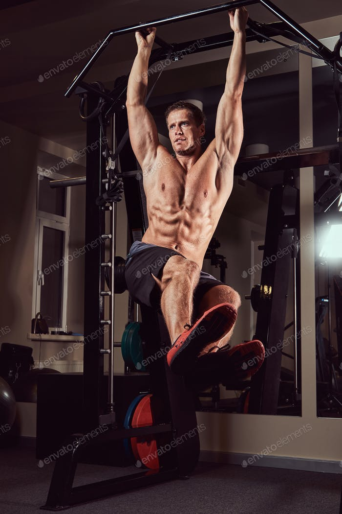 Muscular shirtless man doing exercise on a horizontal bar to strengthen the abdominal muscles.