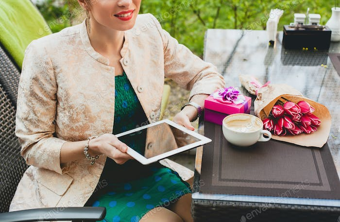 young stylish happy woman sitting in cafe, holding tablet pc