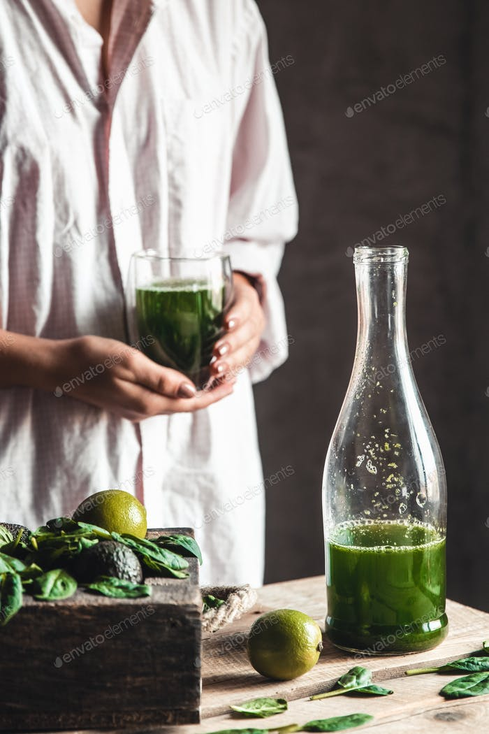 Woman takes a glass of smoothie into a glass, detox, wholesome food, vegan, eco. Body cleansing