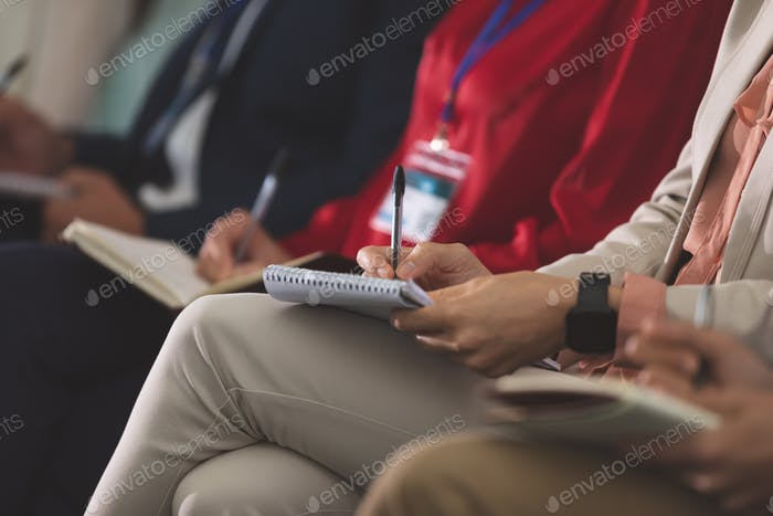 Business people writing on notepad in a business seminar in office building