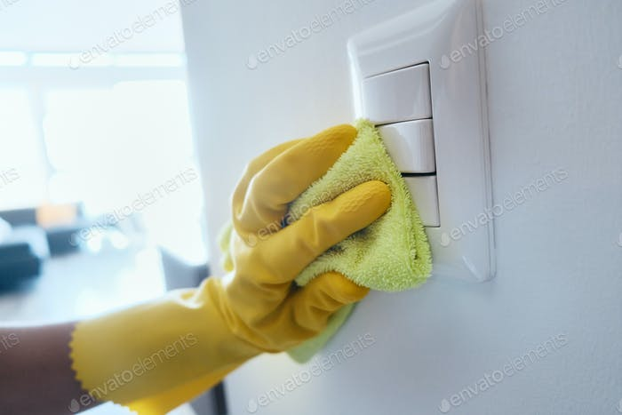 Person Cleaning And Disinfecting Electric Switches