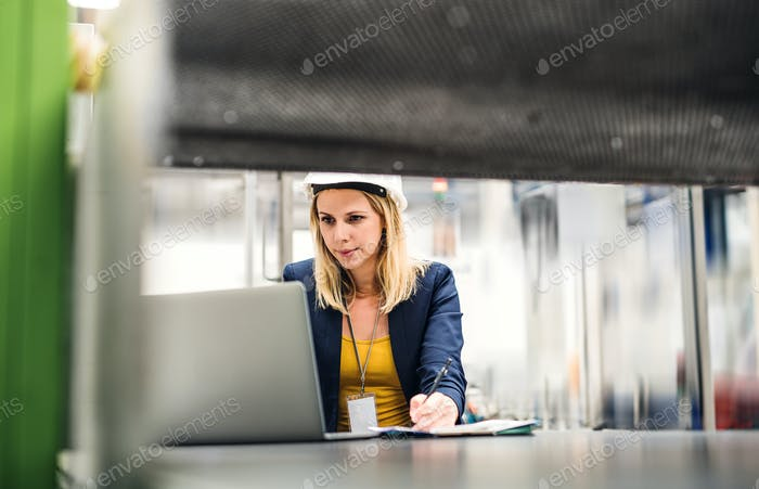 A portrait of an industrial woman engineer in a factory using laptop.