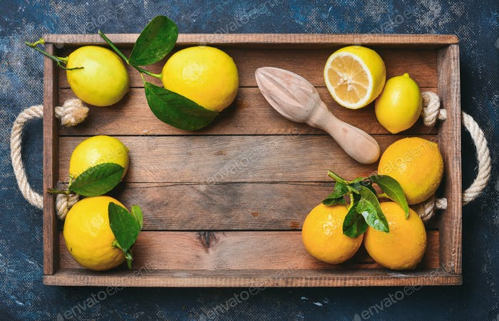 Freshly picked lemons with leaves in wooden box