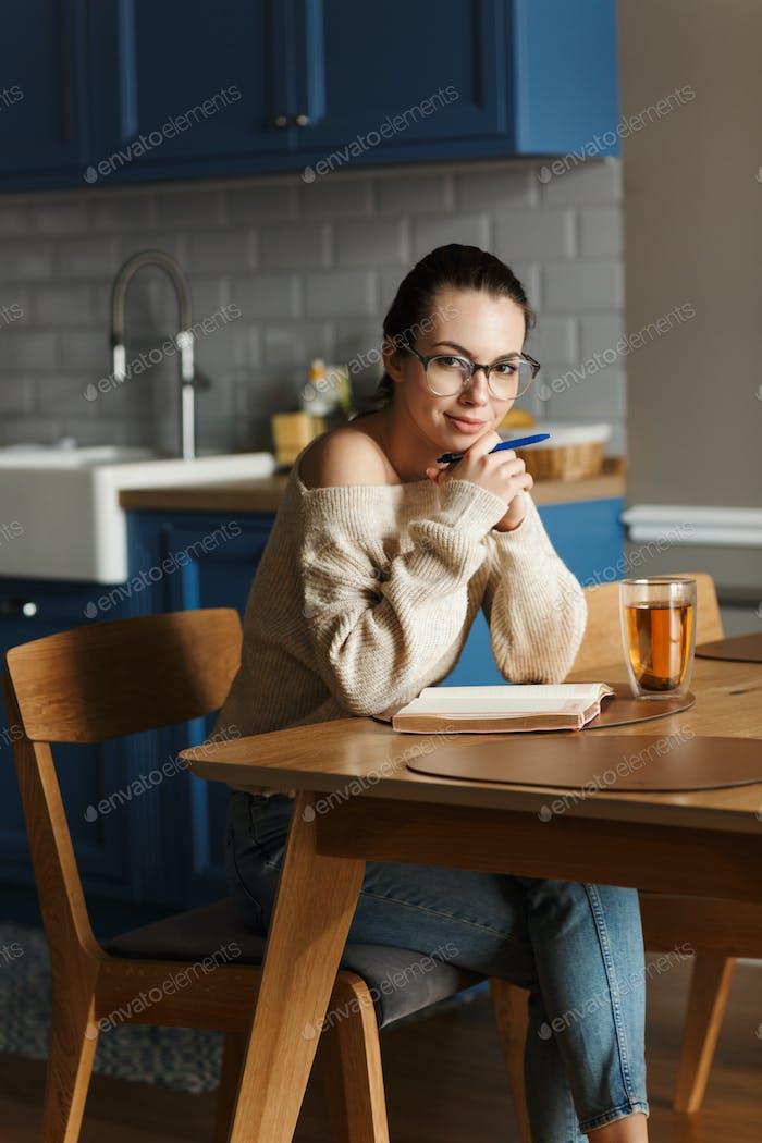Mujer optimista bebiendo té escribiendo notas en cuaderno.