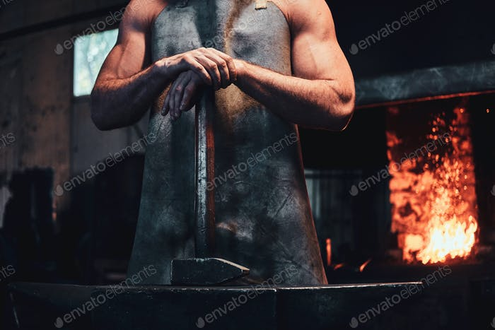Strong blacksmith is posing for photographer at his workshop