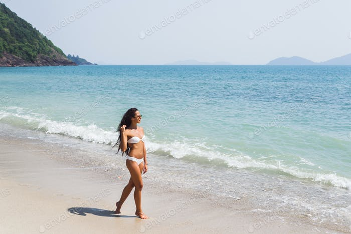 Beautiful thin woman with long black hair walking by the amazing white sand beach