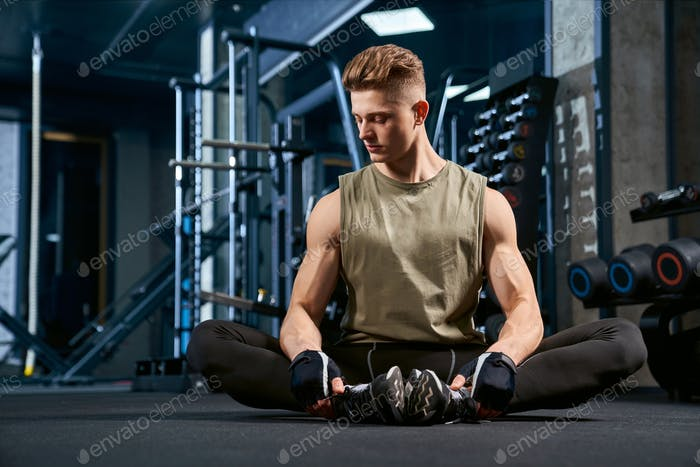 Man doing butterfly stretch on floor in gym