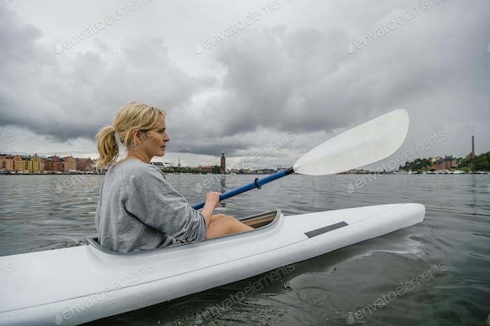 Frau Kajakfahren auf dem Fluss