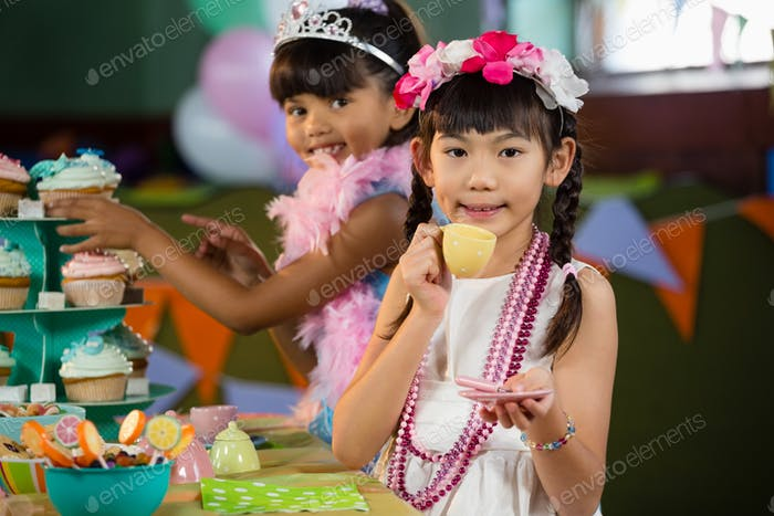 Portrait of cute girls having tea during birthday party