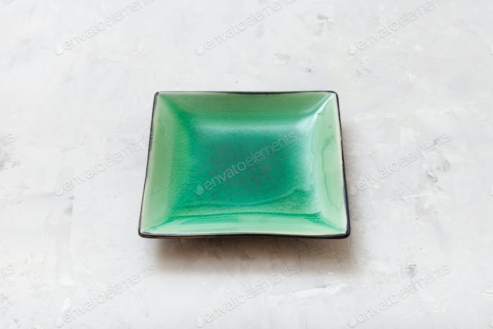 green square saucer on gray concrete board