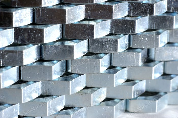 Close-up wall of numerous chrome metal nuts