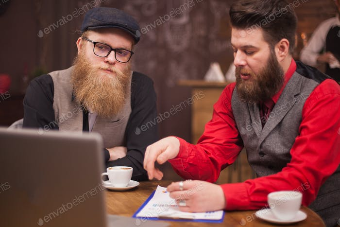Handsome bearded men having business video call on their laptop in a coffee shop