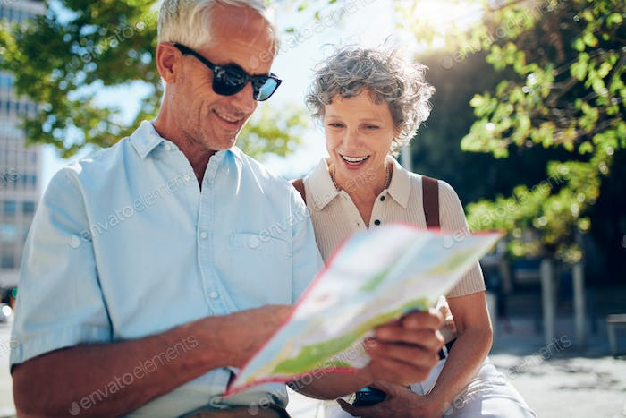 Elderly couple sitting outdoors on a bench and using city map