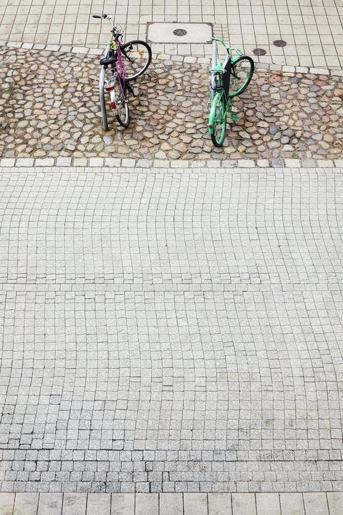 Two bikes parked on cobblestone street pavement.