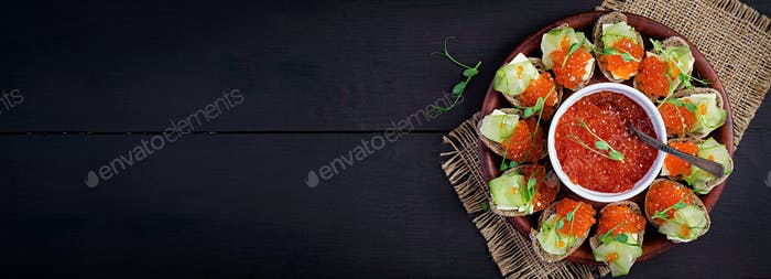 Canape with salmon red caviar. Sandwich for lunch. Delicious food. Top view, banner