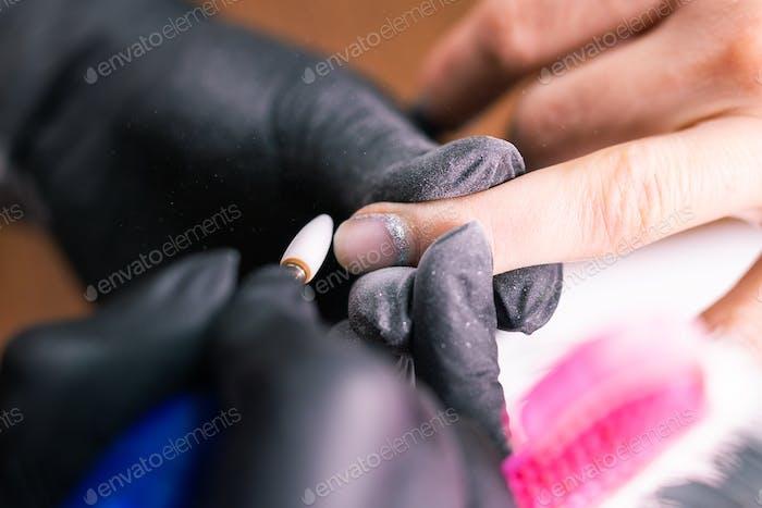 Nahaufnahme einer Maniküristenfrau entfernt Gel-Schellack-Nagellack von den Nägeln des Kunden mit Maniküre
