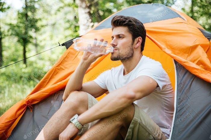 Mann sitzt in der Nähe von touristischen Zelt und Trinkwasser im Wald