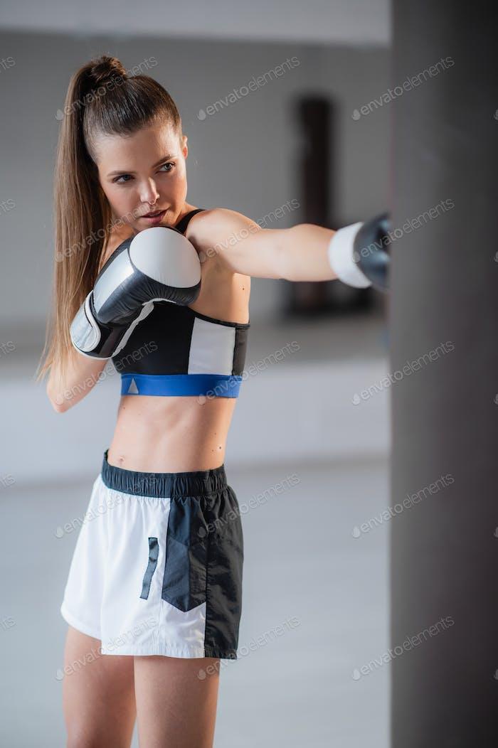 Das Mädchen bereitet sich auf einen Boxwettbewerb vor und trainiert Schläge auf einem Boxsack in einem geräumigen