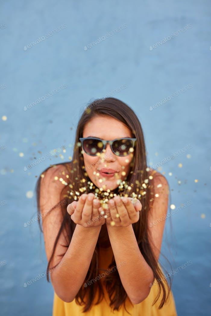 Glückliche junge Frau bläst Konfetti in der Luft