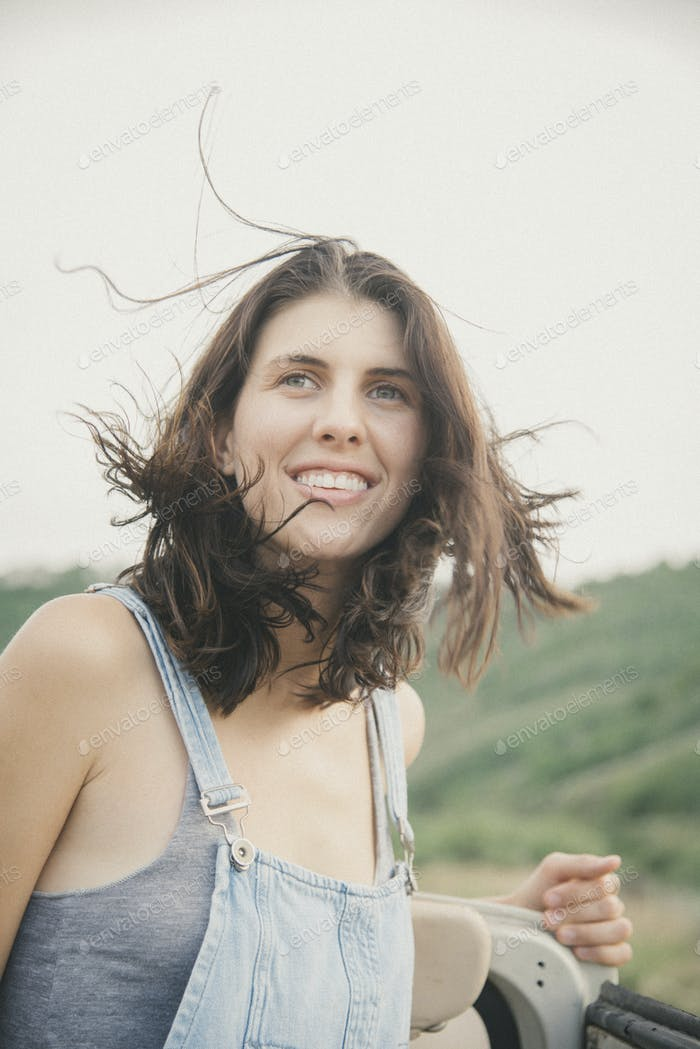 A young woman with windblown hair in dungarees in the mountains.