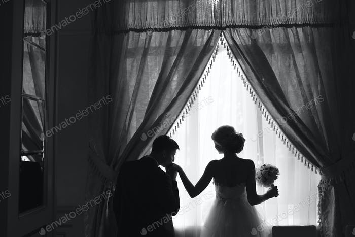 bride and groom standing in front of window