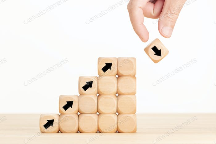 Hand and wooden block with falling arrow