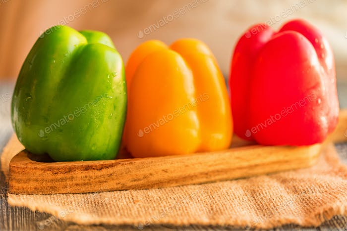 Variety of bell paprika peppers on cutting board