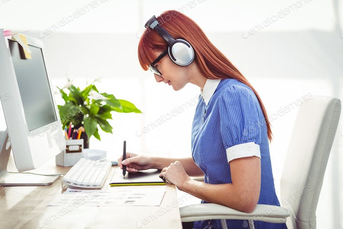 Attractive hipster woman with headset using graphics tablet in her office
