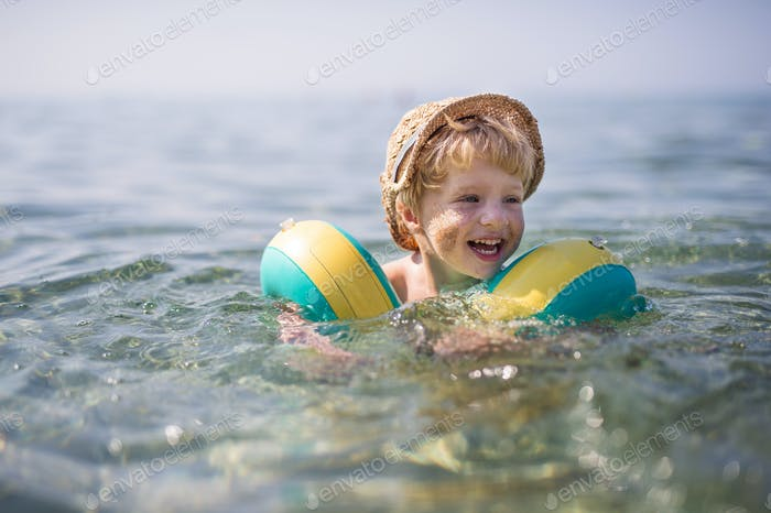 A small toddler boy with armbands swimming in water on summer holiday.