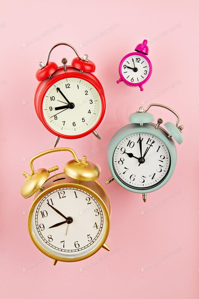 Collection of bright colorful alarm clocks over the pink background