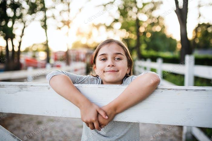 Ein Porträt von kleinen Mädchen auf Familienfarm, stehend durch Holztor